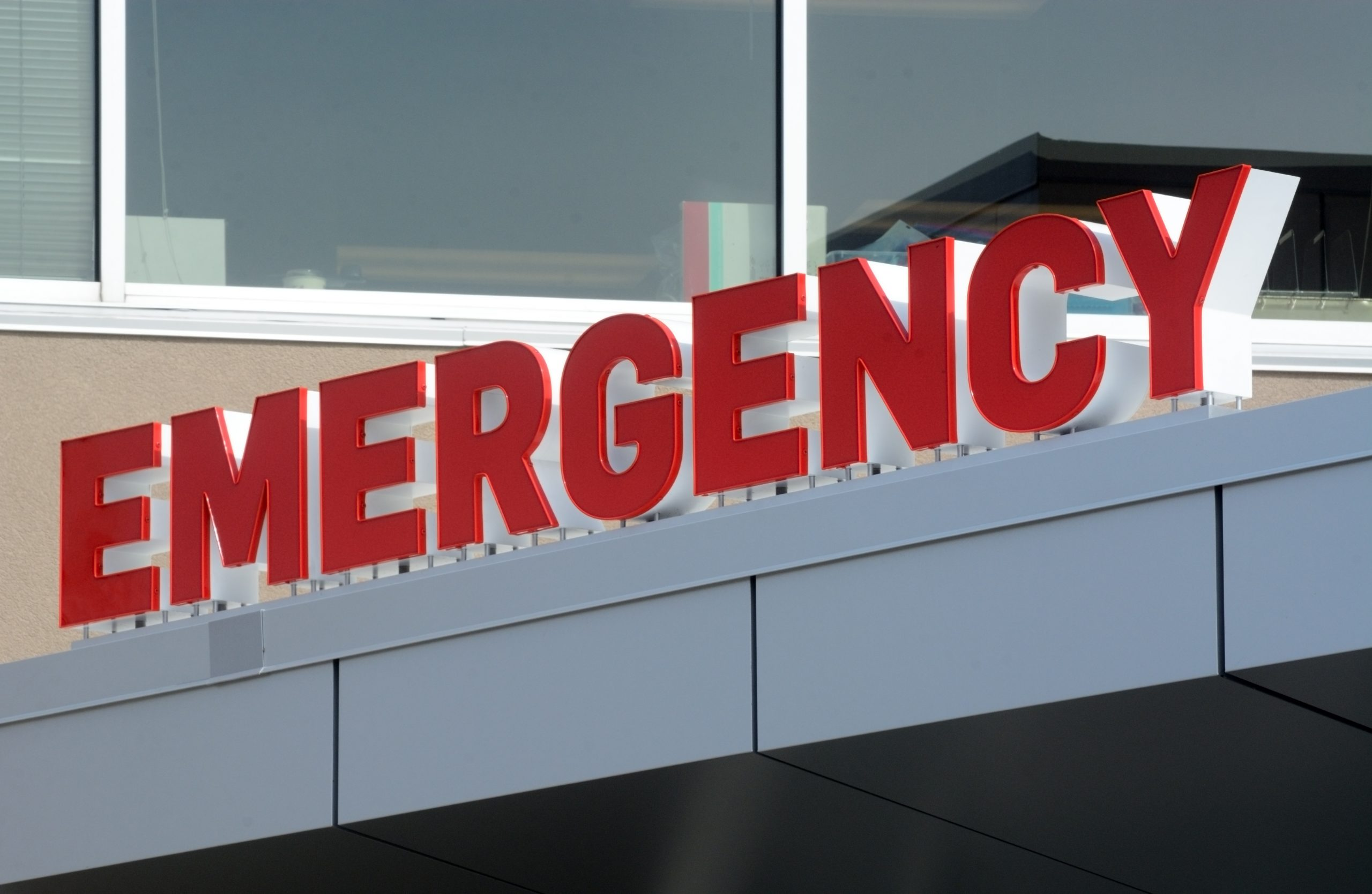 Emergency sign on building entrance for emergency services at Caledonia animal hospital.